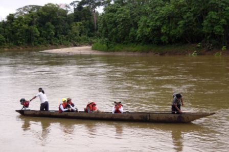 canoe on river with western and indigenous people